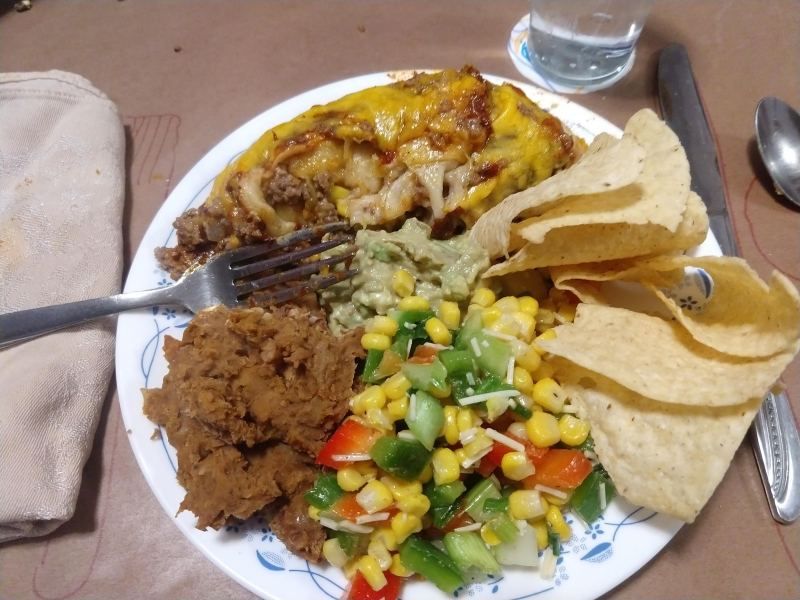 Beef enchiladas, corn chips with guac, corn salad, and refried beans