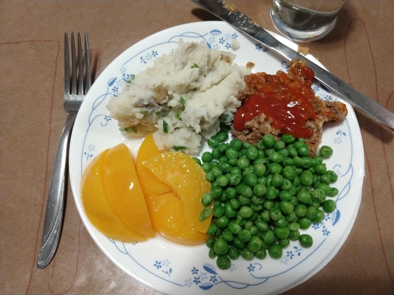 Meatloaf, mashed potatoes, green peas, and canned peaches