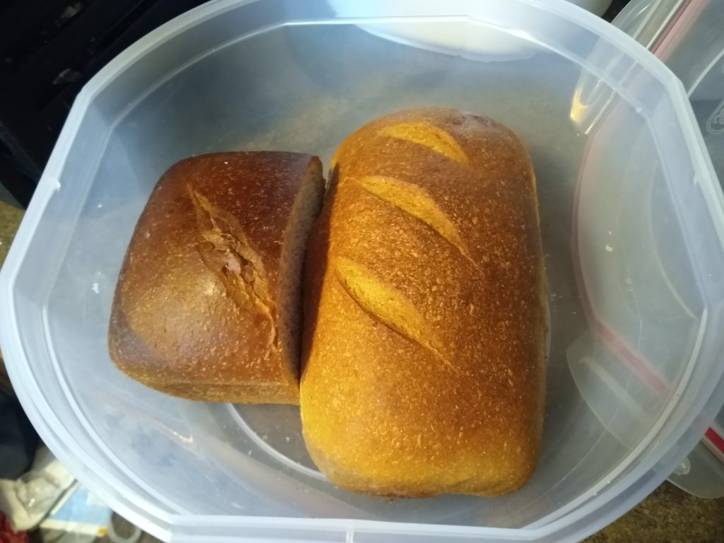 A half eaten loaf of faux-buttermilk bread and a full loaf of half-whole-wheat sourdough bread waiting to be eaten